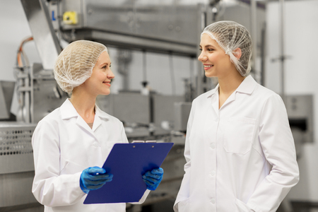 Photo for manufacture, industry and people concept - happy women technologists with clipboard at ice cream factory shop - Royalty Free Image