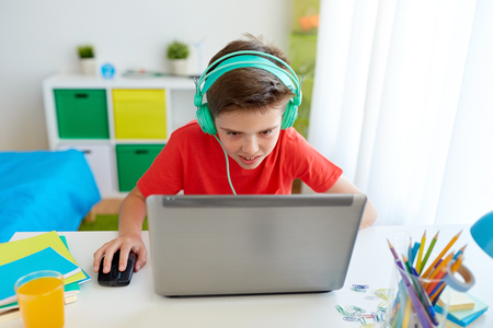 Foto de cyberbullying, gaming and people concept - boy in headphones playing video game on laptop computer at home - Imagen libre de derechos