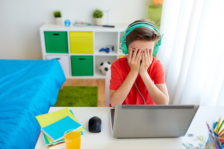 Foto de technology, gaming, cyberbullying and people concept - upset boy in headphones with laptop computer at home lost video game or suffer of bullying - Imagen libre de derechos
