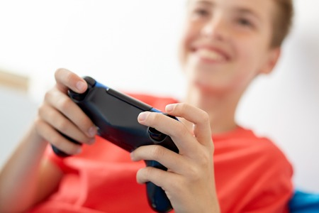 Photo for gaming, technology and people concept - close up of smiling boy with gamepad playing video game at home - Royalty Free Image