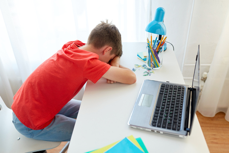 Photo pour tired or sad student boy with laptop at home - image libre de droit