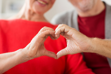 Photo pour close up of senior couple showing hand heart sign - image libre de droit