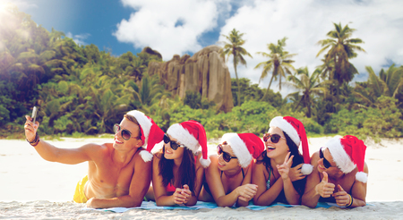 Photo for group of friends in santa hats with taking selfie - Royalty Free Image
