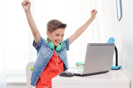 Photo pour boy with headphones playing video game on laptop - image libre de droit