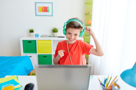 Foto per boy in headphones playing video game on laptop - Immagine Royalty Free