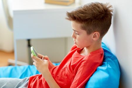 Foto de boy with smartphone lying on bed at home - Imagen libre de derechos