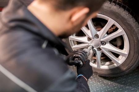 Foto de auto mechanic with screwdriver changing car tire - Imagen libre de derechos