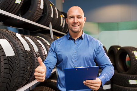 Foto per auto business owner and wheel tires at car service - Immagine Royalty Free