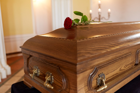 Foto de funeral and mourning concept - red rose flower on wooden coffin in church - Imagen libre de derechos