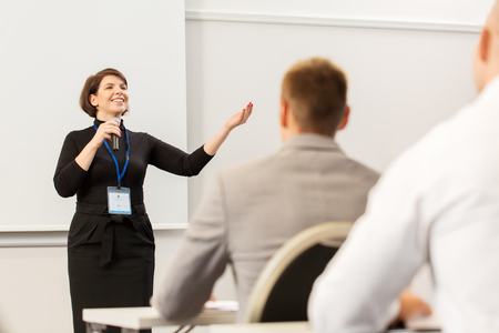 Foto de business, education and people concept - smiling businesswoman or lecturer with microphone talking to group of students at conference presentation or lecture - Imagen libre de derechos