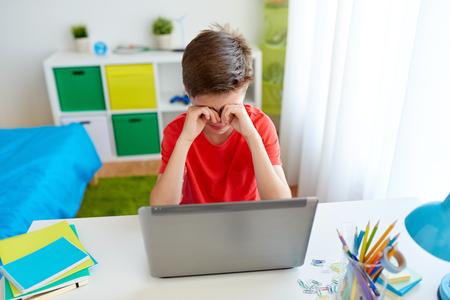 Foto de tired student boy with laptop computer at home - Imagen libre de derechos