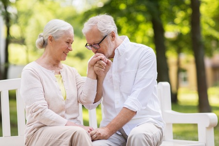 Foto de happy senior couple sitting on bench at park - Imagen libre de derechos