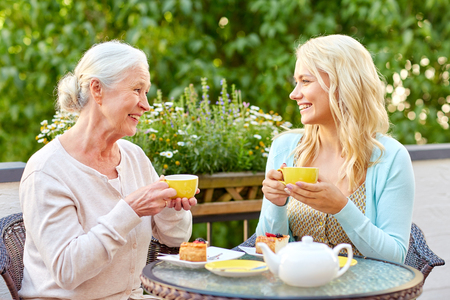 Photo pour daughter with senior mother drinking tea at cafe - image libre de droit