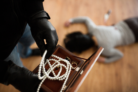 Photo pour criminal with knife and jewelry at crime scene - image libre de droit