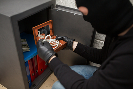 Foto de thief stealing valuables from safe at crime scene - Imagen libre de derechos