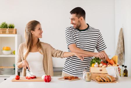 Photo pour happy couple cooking food at home kitchen - image libre de droit