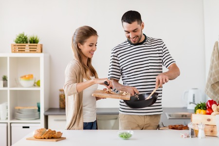 Foto de couple cooking food at home kitchen - Imagen libre de derechos