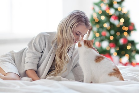 Photo pour happy young woman with cat in bed at christmas - image libre de droit