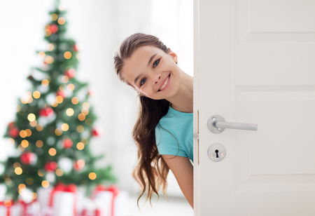 Photo for happy smiling beautiful girl behind door at home - Royalty Free Image