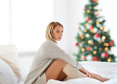 Photo pour happy young woman sitting in bed at christmas - image libre de droit