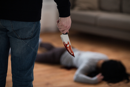 Foto de criminal with knife and dead body at crime scene - Imagen libre de derechos
