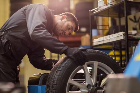 Photo pour auto mechanic balancing car wheel at workshop - image libre de droit
