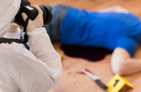 Photo for criminalist photographing dead body at crime scene - Royalty Free Image