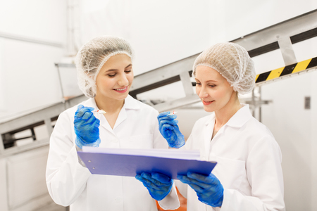 Foto de women technologists tasting ice cream at factory - Imagen libre de derechos