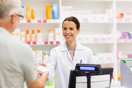 Foto de apothecary selling drug to senior man at pharmacy - Imagen libre de derechos