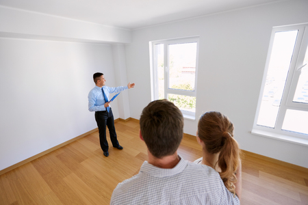 Foto de realtor with clipboard and couple at new home - Imagen libre de derechos