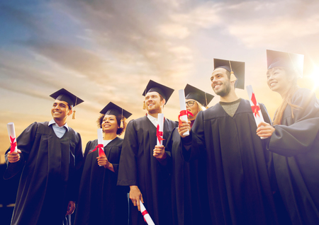 Photo for happy students in mortar boards with diplomas - Royalty Free Image