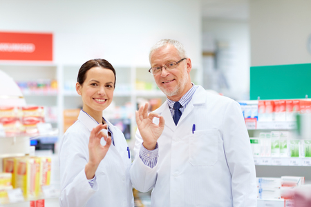 Photo for apothecaries at pharmacy showing ok hand sign - Royalty Free Image