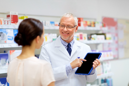 Foto de apothecary and customer with tablet pc at pharmacy - Imagen libre de derechos