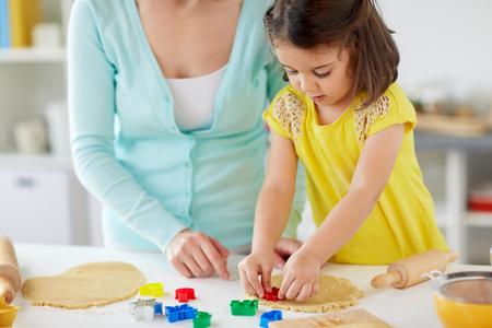 Foto de happy mother and daughter making cookies at home - Imagen libre de derechos