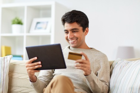 Photo for smiling man with tablet pc and credit card at home - Royalty Free Image