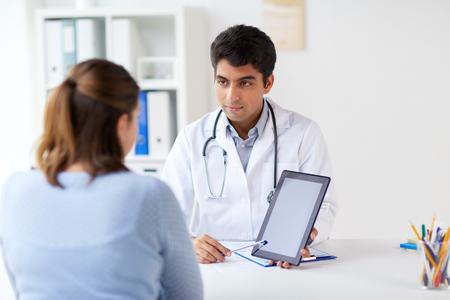 Foto de doctor showing tablet pc to patient at clinic - Imagen libre de derechos