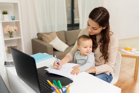 Foto de happy mother with baby and papers working at home - Imagen libre de derechos