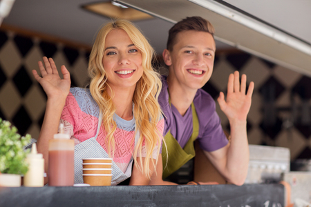 Photo for happy young sellers waving hands at food truck - Royalty Free Image