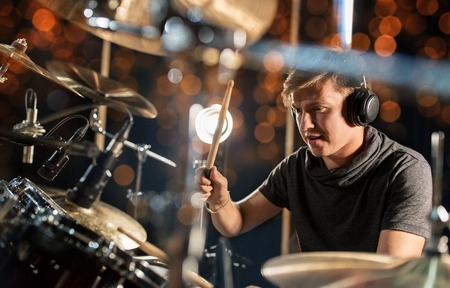Photo for music, people, musical instruments and entertainment concept - male musician in headphones with drumsticks playing drum kit at concert or studio over holidays lights background - Royalty Free Image