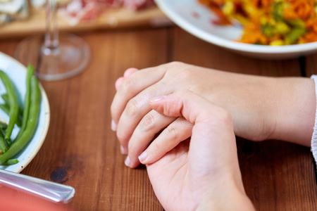 Photo pour people, relationships and eating concept - hands of people sitting at table with food and praying before meal - image libre de droit