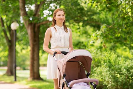 Foto de family, motherhood and people concept - happy mother with child sleeping in stroller walking at summer park - Imagen libre de derechos