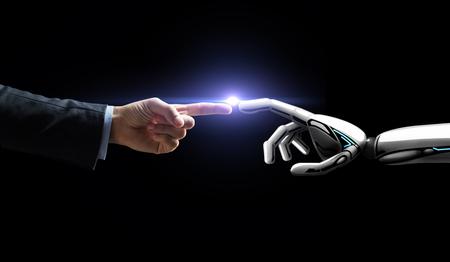 Foto de robot and human hand flash light over black - Imagen libre de derechos