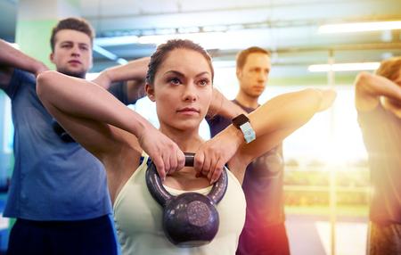 Foto de group of people with kettlebells exercising in gym - Imagen libre de derechos