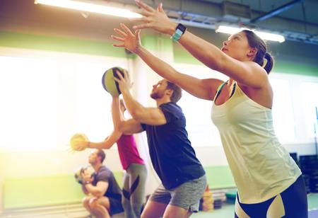 Foto de group of people with medicine ball training in gym - Imagen libre de derechos