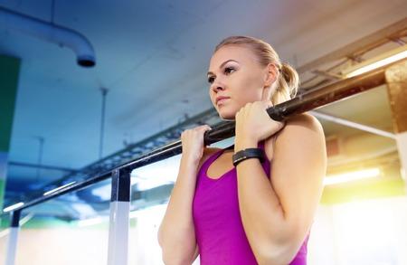 Foto de woman exercising and doing pull-ups in gym - Imagen libre de derechos