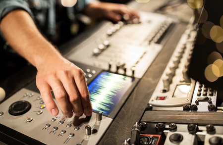 Photo for music, technology, people and equipment concept - man using mixing console in sound recording studio over lights - Royalty Free Image