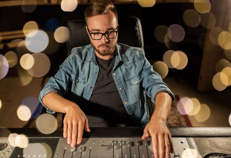 Photo for music, technology, people and equipment concept - man at mixing console in sound recording studio over lights - Royalty Free Image
