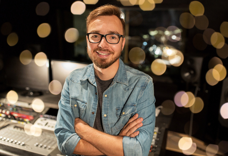 Photo for music, technology, people and equipment concept - happy smiling man at mixing console in sound recording studio over lights - Royalty Free Image