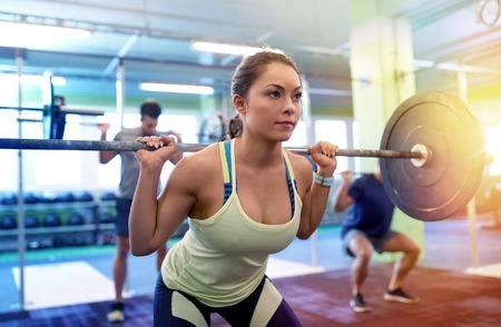 Foto de group of people training with barbells in gym - Imagen libre de derechos