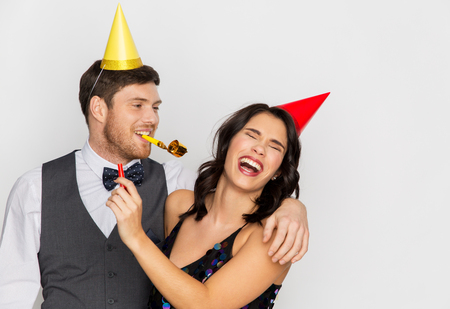 Photo pour happy couple with party blowers having fun - image libre de droit